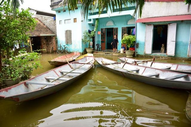 Nước đã rút khá nhiều nhưng nhiều gia đình vẫn còn ngập quanh nhà, người dân phải đi lại bằng thuyền.