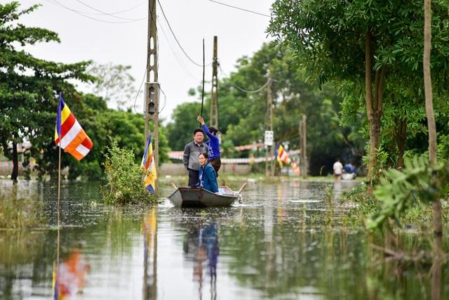Con đường từ thôn ra đường cái lớn vẫn ngập sâu, người dân phải đi lại bằng thuyền.