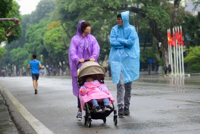 Thời tiết mưa phùn và lạnh là lý do chính khiến lượng khách đổ vể phố đi bộ giảm sút. Một gia đình vẫn mặc áo mưa đi dạo trong khi co ro vì lạnh.