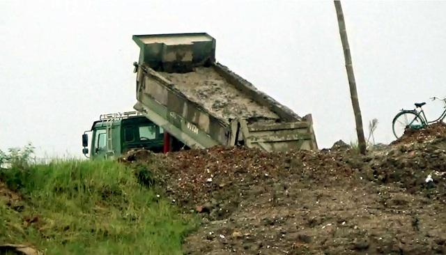 Xe tải chở bùn thải độc hại đổ xuống sông Hồng.