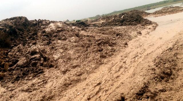 Bùn thải chất đầy ven sông, được xe ủi, máy xúc san gạt xuống sông.