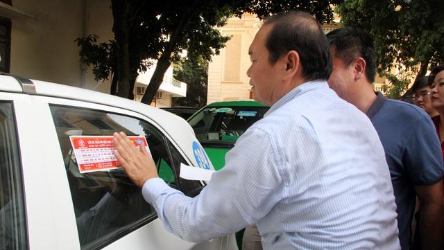 Ông Hà Huy Quang - Phó Giám đốc Sở GTVT Hà Nội tự tay dán đề can cho xe taxi.