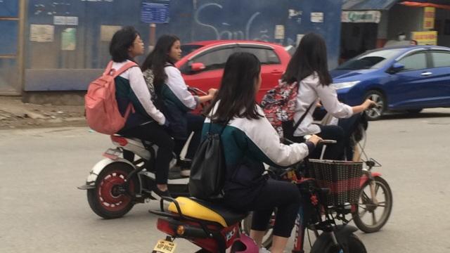 Học sinh Hà Nội vẫn đầu trần đi xe máy điện và vô tư dàn hàng ngang trên đường (ảnh: Mỹ Hà)