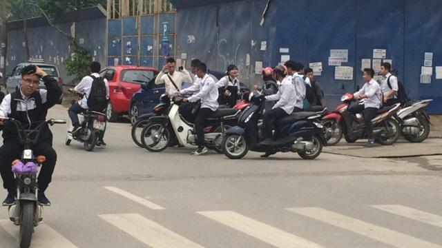 Học sinh tràn vào con ngõ đối diện Trường THPT Nguyễn Trãi, Ba Đình, Hà Nội lấy xe máy và phóng ra đường khi không đội mũ bảo hiểm (ảnh: Mỹ Hà)