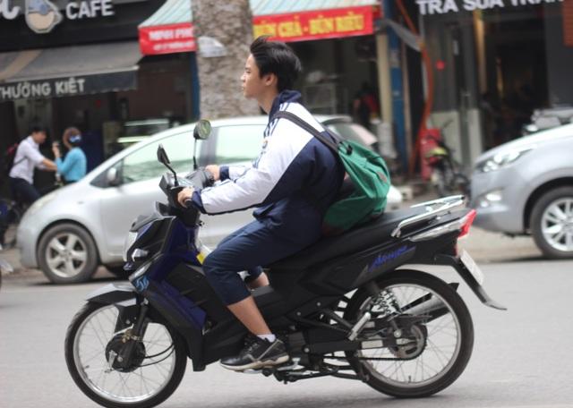 """Em Hường (học sinh của một trường THPT thuộc quận Bắc Từ Liêm) cho biết: """"Trường em cũng có kha khá bạn đi xe máy…Nhà trường có cấm nhưng không được."""" Hường cũng cho hay, không phải học sinh nào đi xe máy, xe đạp điện cũng đội mũ bảo hiểm. (Ảnh chụp vào ngày 7/4/2017 trên đường Lý Thường Kiệt)"""