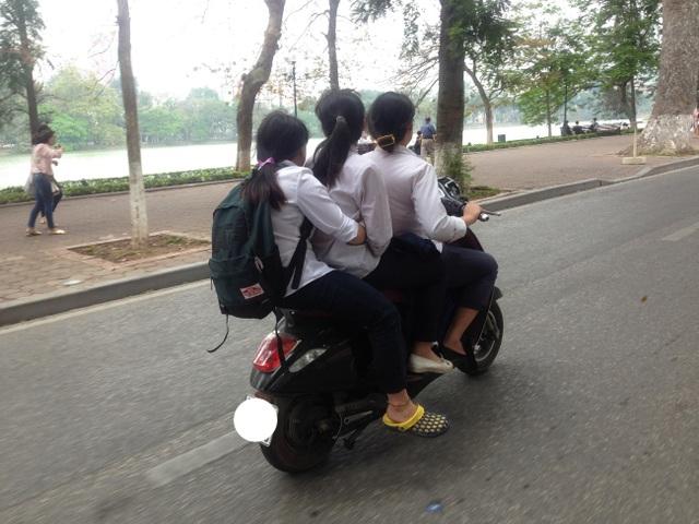 Học sinh đi xe gắn máy, chở ba và không đội mũ bảo hiểm vẫn nhởn nhơ tham gia giao thông. (Ảnh chụp trên đường Đinh Tiên Hoàng vào ngày 7/4/2017)