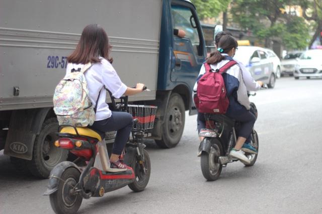 Theo Khoản 4, Điều 8, Nghị định 171/2013/NĐ/CP của Chính phủ, cả người khiển xe đạp điện và người ngồi trên xe đạp điện nếu không đội mũ bảo hiểm sẽ bị phạt tiền từ 100.000 đồng đến 200.000 đồng.(Ảnh chụp vào ngày 7/4/2017 trên đường Hai Bà Trưng)