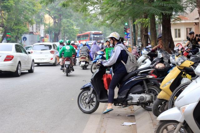 Học sinh đang lấy xe máy từ một điểm trông giữ xe trên vỉa hè. (Ảnh chụp vào ngày 7/4/2017)