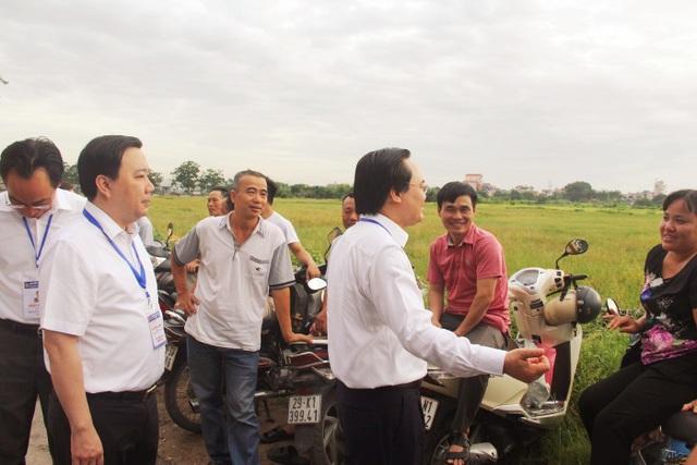 Bộ trưởng dừng lại bên đường hỏi thăm các vị phụ huynh đang chờ con trước cổng trường.