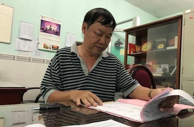 Trung tá Nguyễn Văn Sơn, đội trưởng Đội CSGT huyện Nhà Bè cùng bộ hồ sơ Đăng ký xe của anh B. trong buổi tiếp xúc với PV Dân trí.