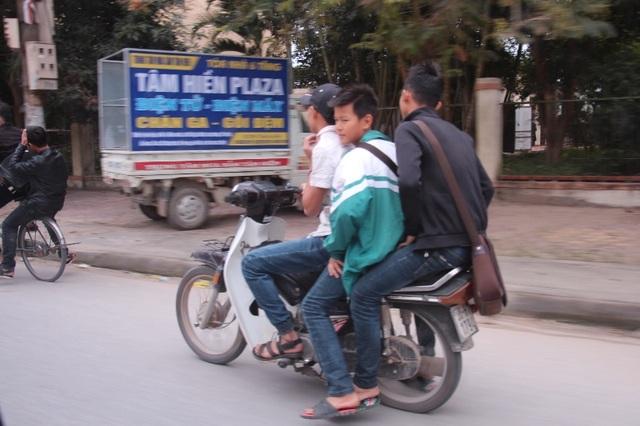 Thậm chí nhiều em học sinh đi xe máy kẹp 3, đầu trần nghênh ngang trên đường như thế này