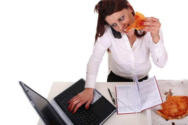 Ăn quá nhanh, vừa ăn vừa làm là thói quen khó bỏ của nhiều người làm công việc văn phòng.