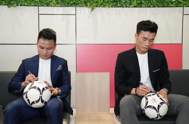 Bùi Tiến Dũng và Nguyễn Quang Hải kí tặng bóng người hâm mộ tại sự kiện