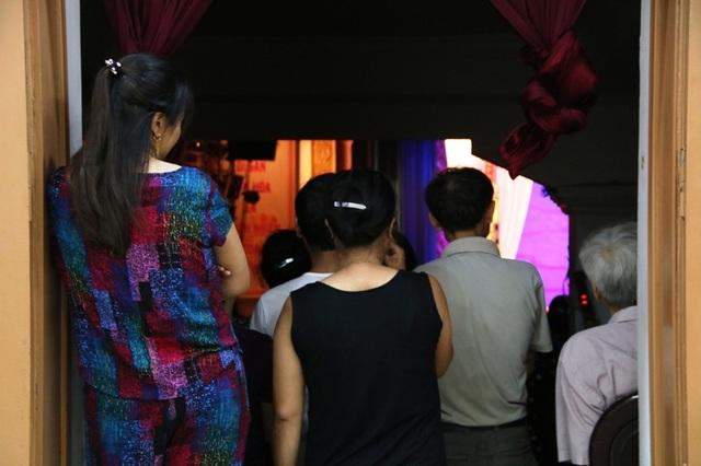 Một số người do đi muộn không có ghế ngồi trong khán phòng phải đứng bên ngoài cửa, lối ra vào không còn chỗ đi.