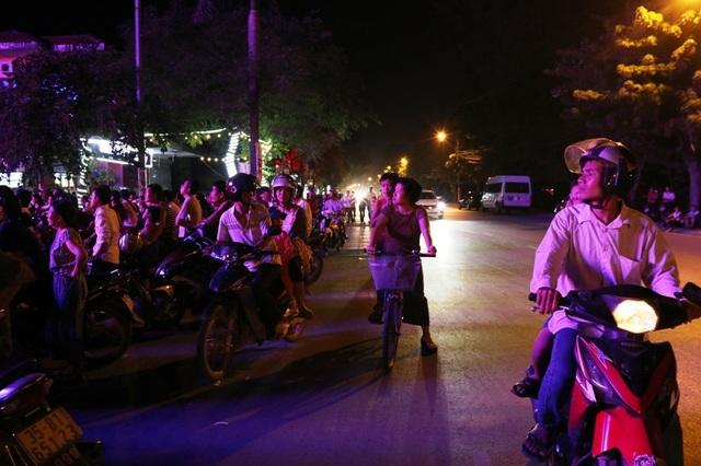 Người dân đi đường cũng dừng lại ngó vào xem các nghệ sĩ biểu diễn.