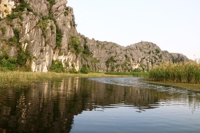 Dòng nước trong xanh mát lành, in bóng những dãy núi đã vôi và cỏ cây.