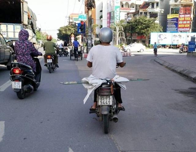 Một chiếc xe máy chở kính có thể gây nguy hiểm cho người đi bên cạnh.