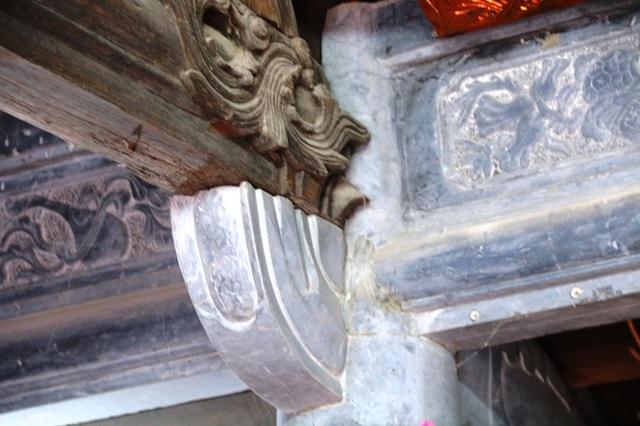Một mối ghép giữa gỗ của phần mái nhà với cột bằng đá, nhìn đơn sơ nhưng rất chắc chắn.