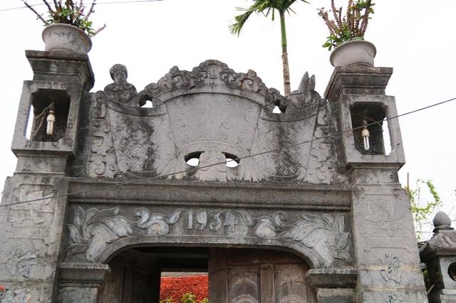 Chiếc cổng đá của ngôi nhà được xây dựng năm 1934, xây sau căn nhà một thời gian dài. Các chi tiết đá trạm khắc trên chiếc cổng này đã bạc màu thời gian, rêu mốc bám đầy.