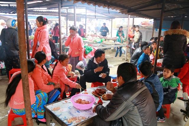 Nhiều người đi chợ sắm Tết, tranh thủ ghé vào một hàng ăn vặt để giải lao. Xúc xích, bánh rán, thịt nướng là những món ăn được mọi người ưa thích.