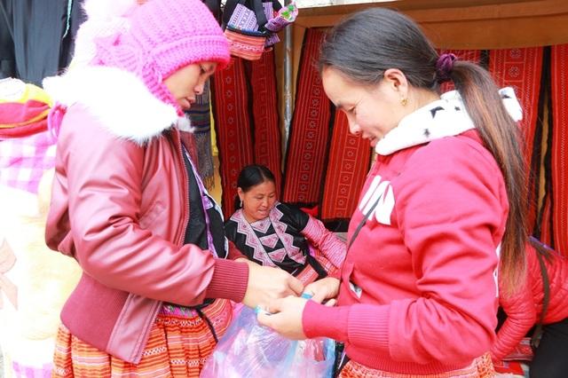 Hai người phụ nữ sau khi mua được những món đồ ưng ý khoe với nhau sau những giờ dong duổi khắp chợ để sắm đồ Tết cho gia đình.