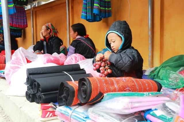 Em bé đến chợ bán hàng cùng mẹ được trả thù lao bằng một chùm nho, đang chọn lựa từng quả để ăn.