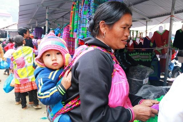 Nhiều phụ nữ đến chợ từ rất sớm, địu theo cả con nhỏ sau lưng. Ánh mắt của đứa trẻ ngơ ngác vì lần đầu tiên trong đời được đi chợ - nơi có nhiều người nhộn nhịp mua bán, trao đổi hàng hóa.