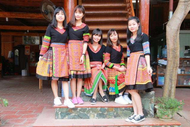 Các bạn sinh viên Hà Nội diện váy dân tộc chụp ảnh lưu niệm bên bậc thang nhà sàn
