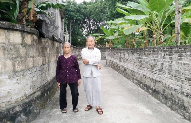 Vợ chồng ông Chiều bên con đường có sự góp đất của gia đình.