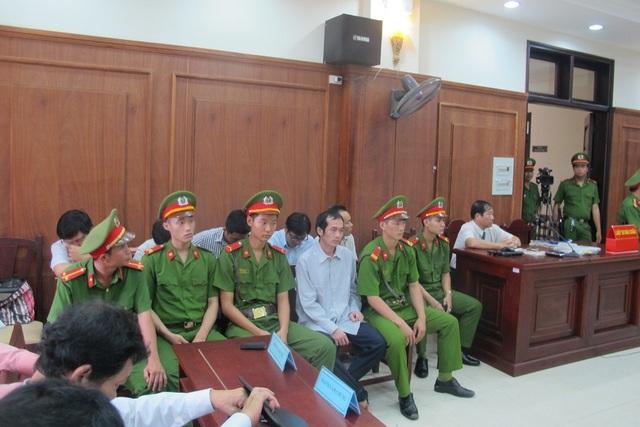Các bị cáo tại phiên tòa (ngồi giữa và sau lưng lực lượng công an)