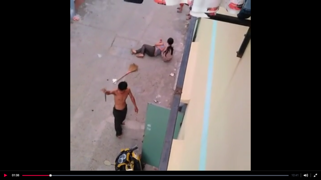 Quang dùng dao cứa cổ vợ khiến chị này ngã gục xuống đường (ảnh chụp lại từ clip)