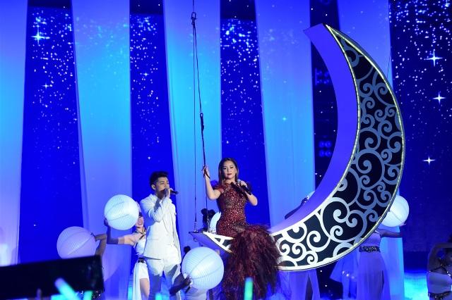 """Tiết mục được đầu tư hoành tráng khi HLV Minh Tuyết cất tiếng hát từ trên """"siêu mặt trăng"""" trong khi đó, Noo Phước Thịnh lịch lãm đứng phía dưới ánh trăng"""