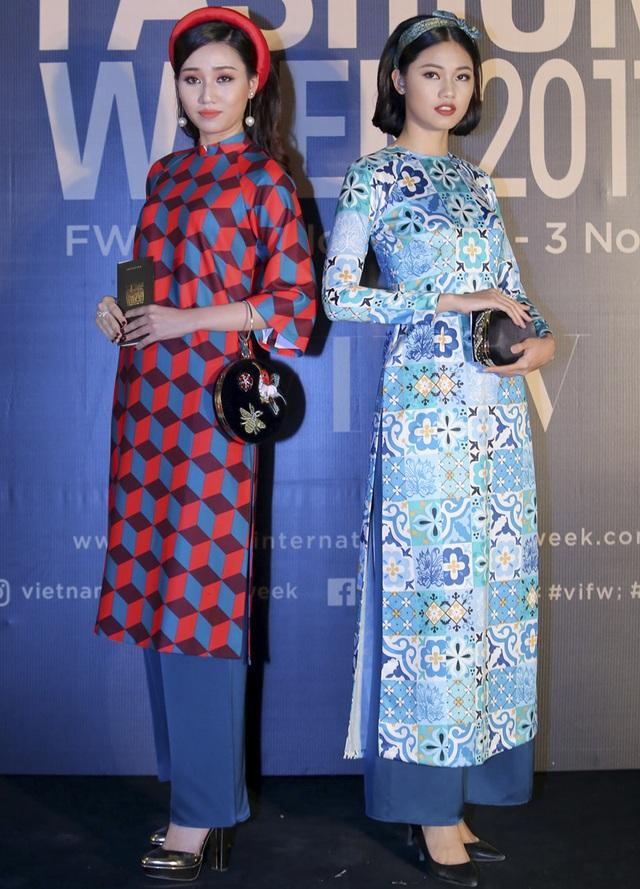 Cặp chị em Á hậu Ngô Trà My – Ngô Thanh Thanh Tú xuất hiện nền nã trong tà áo dài cách tân. Cả 2 lựa chọn nhiều phụ kiện như hoa tai ngọc trai, bóp đầm tròn, giày mũi nhọn,… tạo nên tổng thể hết sức cổ điển, tựa như những quý cô thập niên 50, 60.