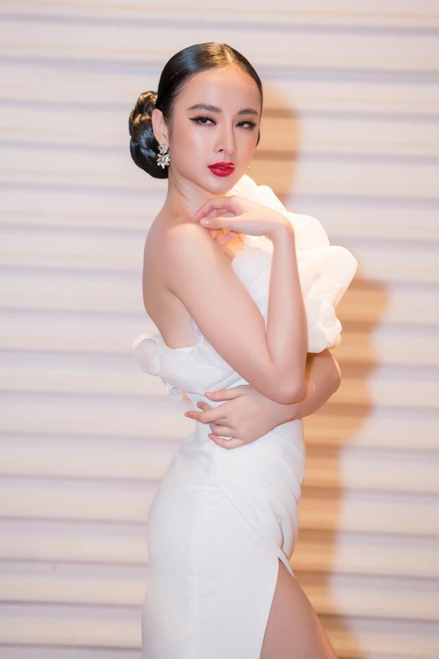 """Tại sự kiện, Angela Phương Trinh sexy, quyến rũ trong bộ váy trắng sẻ sâu, bộ váy bị hở ngực lộ vòng 1 nên người đẹp thường xuyên dùng tay """"che chắn""""."""