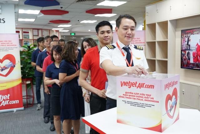 Phó Tổng giám đốc Vietjet Đỗ Xuân Quang (áo đỏ bên trái) và Anh Dương Hoài Nam – Giám đốc văn phòng Miền Bắc, chủ tịch Hội Liên hiệp Thanh niên Vietjet cùng tham gia công tác cứu trợ, gấp rút công tác vận chuyển hàng hóa lên chuyên cơ trước giờ cất cánh.