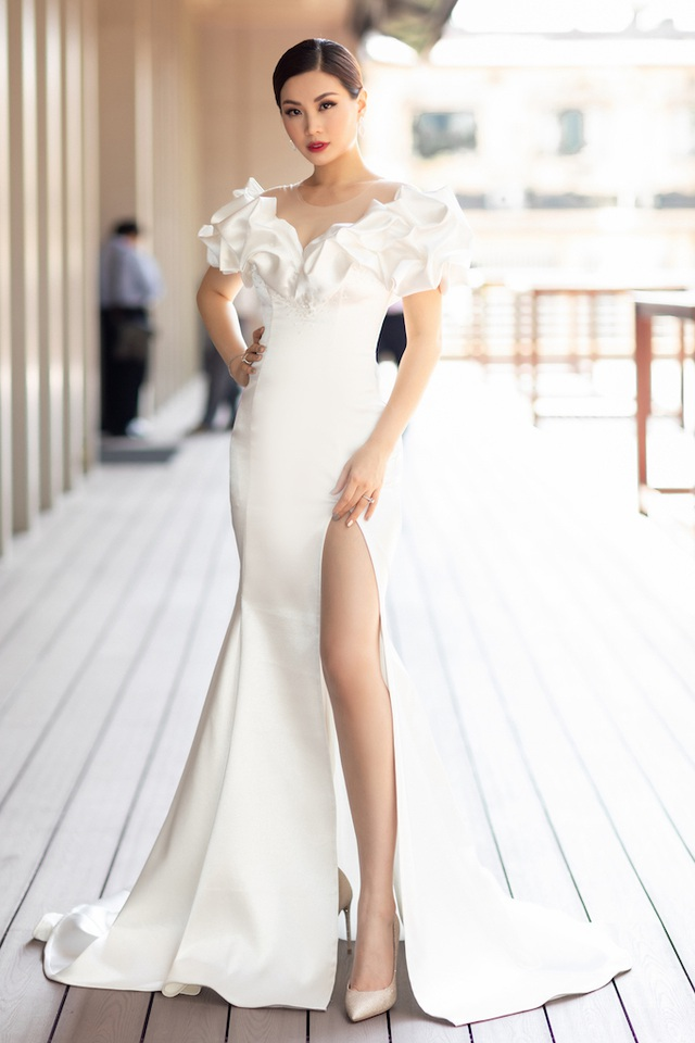 Á hậu Diễm Trang diện đầm trắng với phần vai được tạo hình 3D lạ mắt. Đây là một trong những lần hiếm hoi bà mẹ một con trang điểm sắc sảo đến vậy, với lông mày xếch, môi đỏ thẫm và mái tóc vuốt keo gọn gàng.