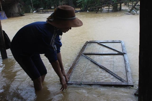 Lũ lên trong đêm, nhiều đồ đạc nhà chị Nguyễn Thị Hiền bị trôi mất. Tranh thủ trời ngớt mưa chị Hiền ra vớt chiếc cửa bị nước lũ cuốn.