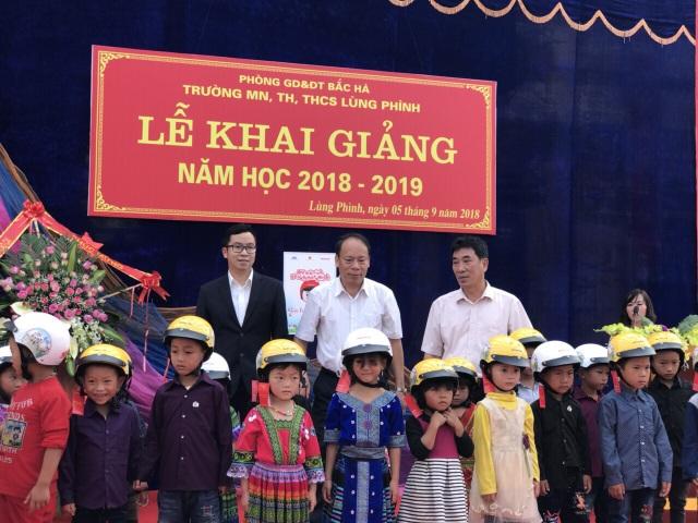 Đại diện Ủy ban ATGT Quốc gia và Công ty Honda Việt Nam trao mũ bảo hiểm cho các em học sinh tại Trường mầm non, Tiểu học và THCS xã Lùng Phình, Lào Cai