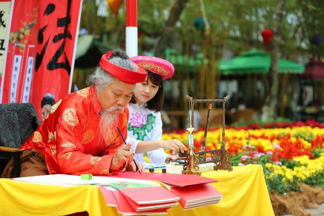 Ông đồ viết chữ thư pháp tặng người dân đến tham quan lễ hội hoa.