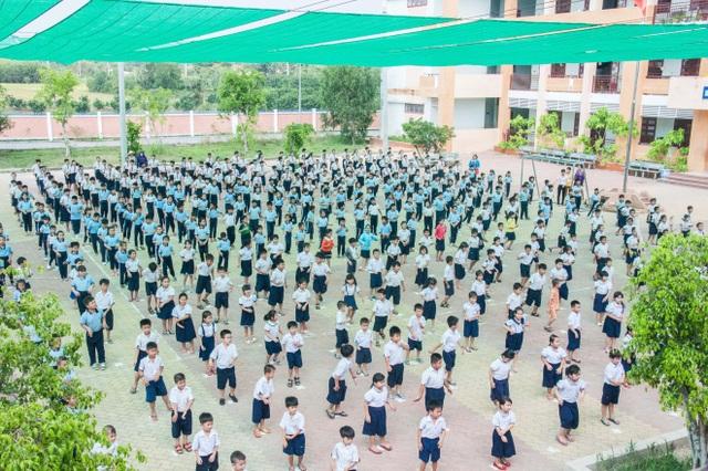 Các em học sinh vui vẻ tập thể dục dưới mái che