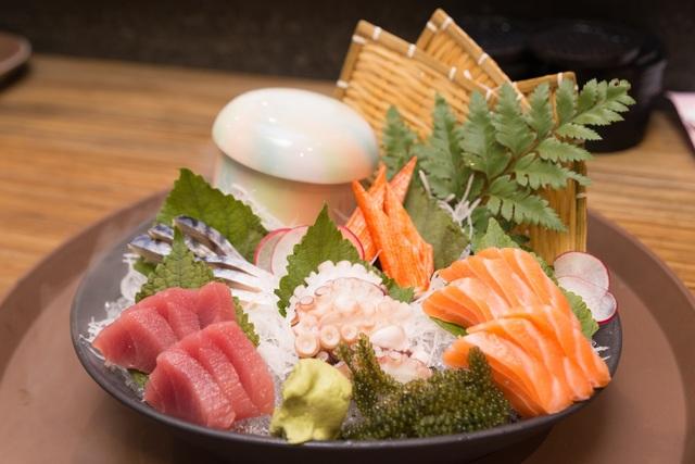 Sushi tổng hợp với cá ngừ, cá hồi, cá basa, thanh cua, rong nho, bạch tuột và trang trí bằng đá khói.