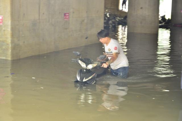 Nhân viên bãi xe dầm mình dưới nước bẩn, tìm và dắt xe ra cho khách