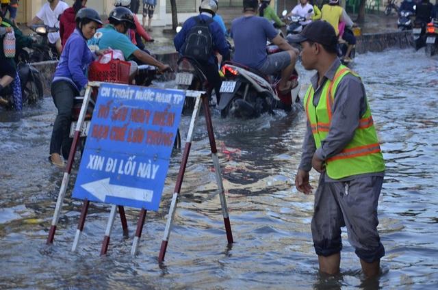 Công nhân thoát nước đứng điều tiết, hướng dẫn người dân di chuyển tránh điểm ngập sâu