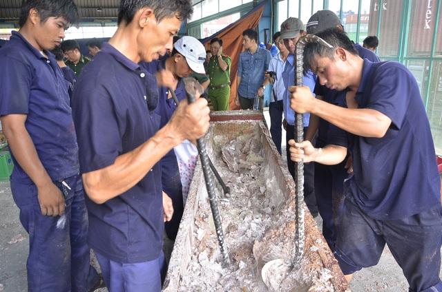 Công nhân tiến hành lấy ngà voi được cất giấu trong khối gỗ