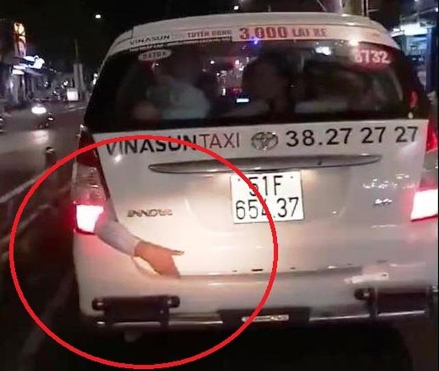 Cánh tay người bị kẹt sau xe taxi khiến người dân xôn xao (ảnh cắt từ clip)
