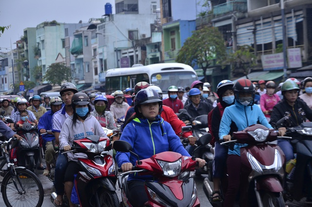 Trên các tuyến đường, người lớn cũng trang phục áo ấm, khăn len khi ra ngoài vào buổi sáng