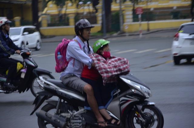 Một em bé được bố choàng áo phía trước để chắn gió lạnh khi chở đến trường