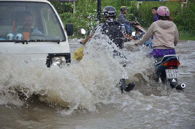 Những lúc ô tô chạy nhanh qua khiến sóng đánh vào người đi xe máy
