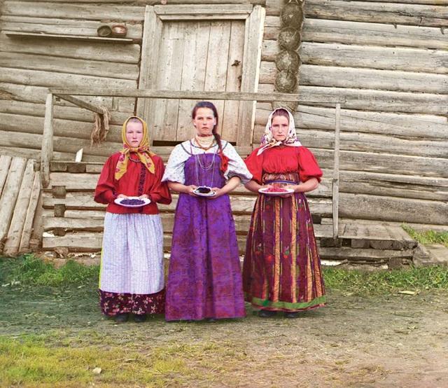 Những thiếu nữ nông thôn ở Nga trong trang phục truyền thống, đứng trước ngôi nhà gỗ. Hình ảnh chụp tại một vùng nông thôn dọc theo bờ sông Sheksna gần thị trấn nhỏ của Kirillov. Ảnh chụp năm 1909.