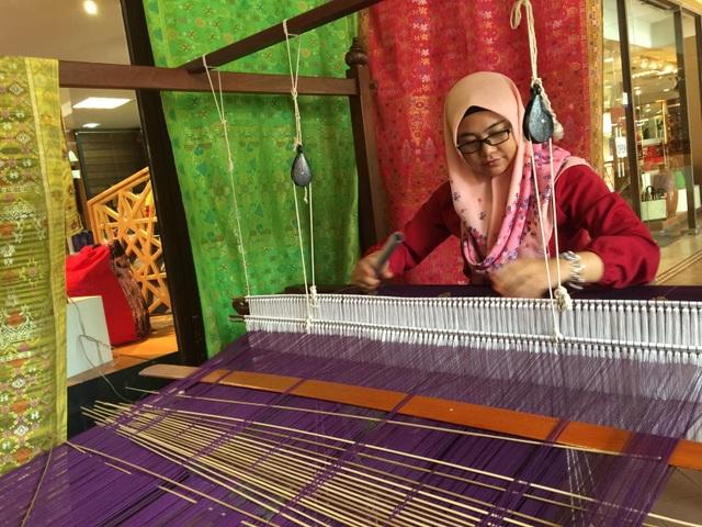 Nghệ nhân dệt vải Songket - một loại vải dệt thủ công bằng sợi chỉ đan xen chỉ vàng, chỉ bạc, tạo thành tấm vải kim tuyến có mẫu mã cầu kỳ
